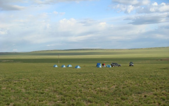 PHOTO: A smattering of light blue tents are dwarfed by the surrounding grassland and sky that stretches on forever.