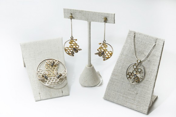 Silver loops with honeycomb interiors support sculpted metal bees on necklace pendants and earrings.