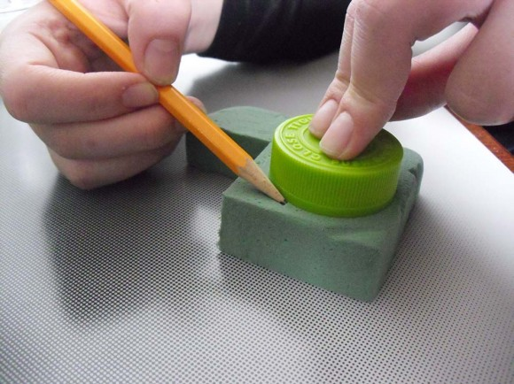 hands tracing around a bottlecap and block of foam with a pencil.