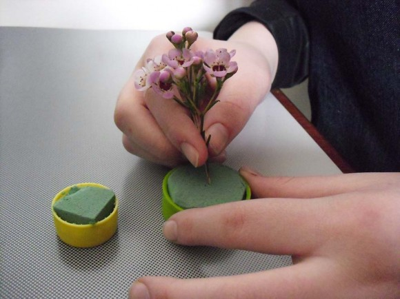 hands poking flowers into floral foam.
