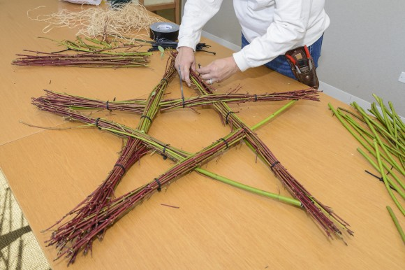 PHOTO: Next, position and secure shorter bundles of twigs until the base is completely covered.
