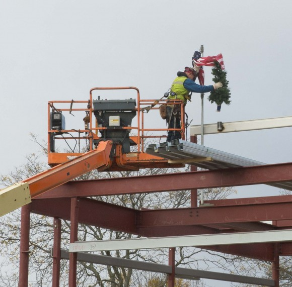 "A construction worker ""tops off"" the site, as the team reaches the halfway point in the construction of the new campus."
