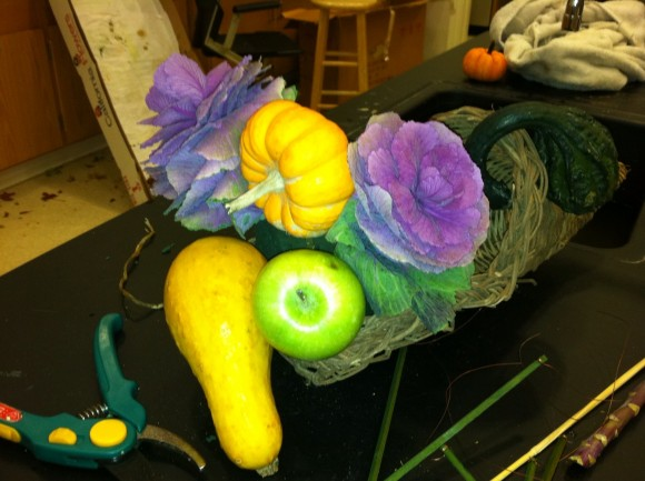 To begin, position the largest items by inserting floral picks into each and anchoring it in the foam.