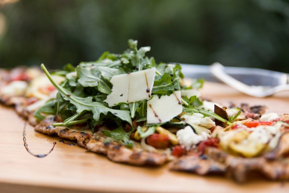 PHOTO: Flatbread with shaved cheese, grilled tomatoes, and balsamic vinegar on baby salad greens.