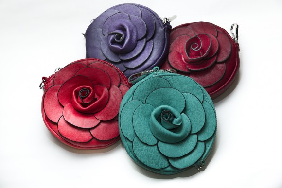 Round, leather clutch purses with decorative roses in jewel tones.