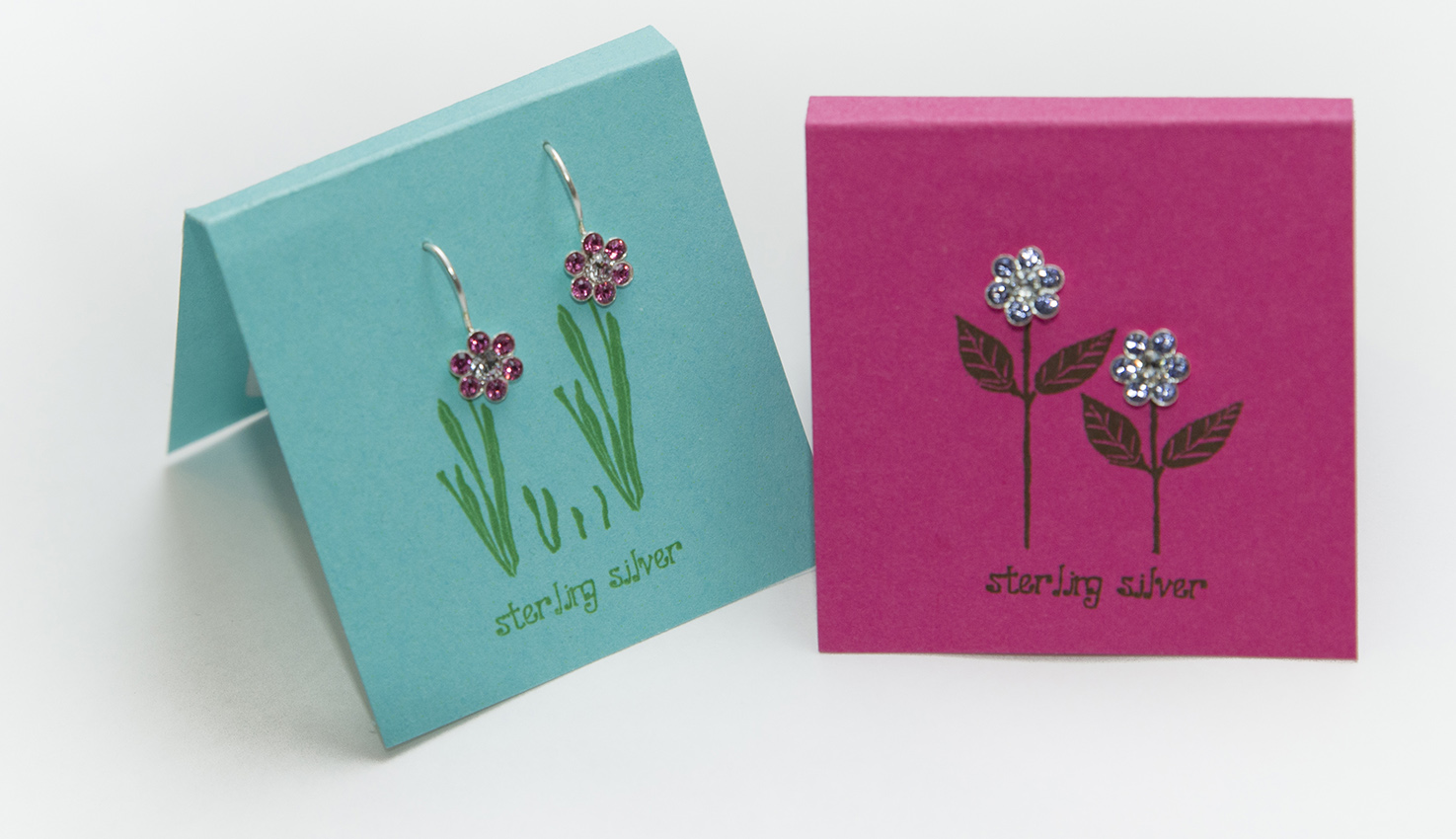 Delicate crystal and sterling silver children's earrings in the shape of 6-petal flowers.