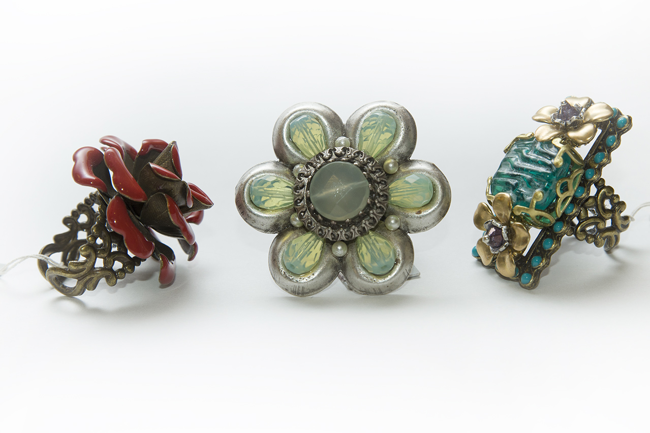 A collection of 3 rings in the shape of various flowers.