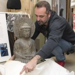 A circa-1900s hand-carved Buddha is unwrapped for display by Gabe Hutchison