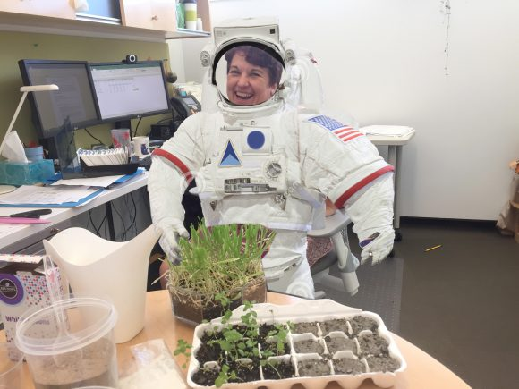 PHOTO: Kathy J. sitting in her office wearing a space suit.