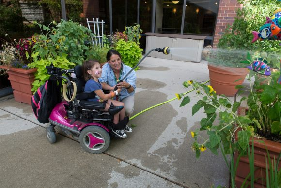PHOTO: Using a watering wand to reach planters.