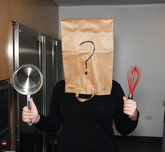 PHOTO: A girl with a bag over her head, holding a pot in her right hand, a whisk in her left.