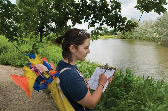 An intern carries a quiver full of marking flags, and takes notes on her clipboard.