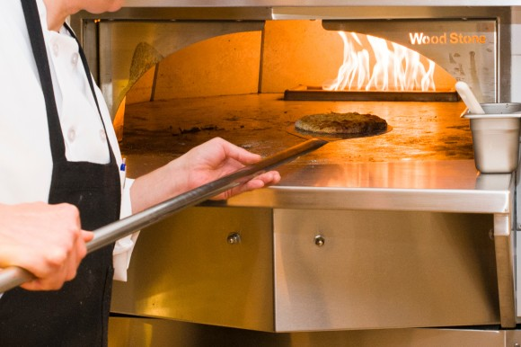 A pizza goes in to the pizza oven.