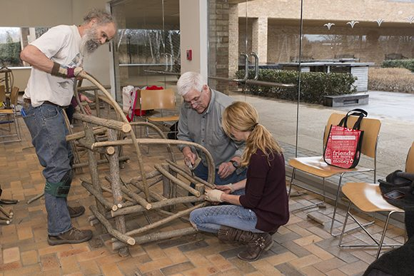 Bim Willow supervises construction on a rustic chair frame.
