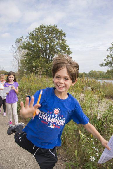 A boy on a field trip runs through the prairie.