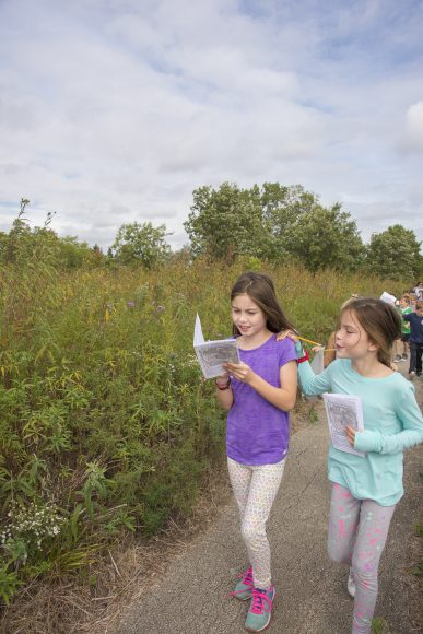 Two girls compare answers as they walk through the prairie on a field trip.