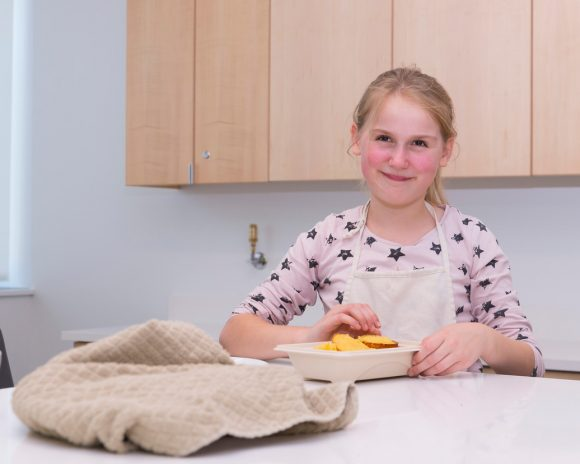 PHOTO: a girls is smiling as she holds the plate of muffins she made, and is going to taste.